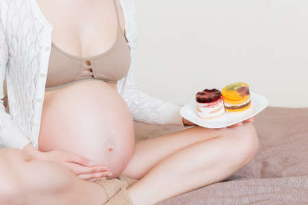 Close up of excited pregnant woman is eating cakes with great pleasure relaxing at home. Enjoying sweet food during pregnancy concept.