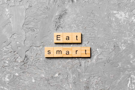 Eat smart word written on wood block. Eat smart text on cement table for your desing, Top view concept. 스톡 콘텐츠