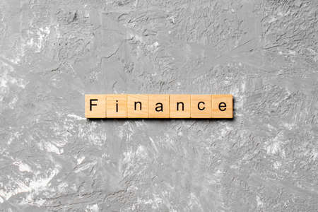 FINANCE word written on wood block. FINANCE text on cement table for your desing, concept.