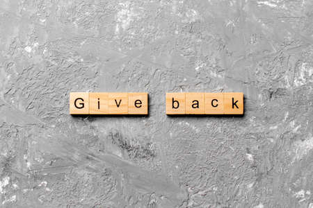 Give Back word written on wood block. Give Back text on table, concept.