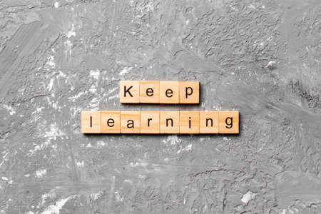 keep learning word written on wood block. keep learning text on table, concept.