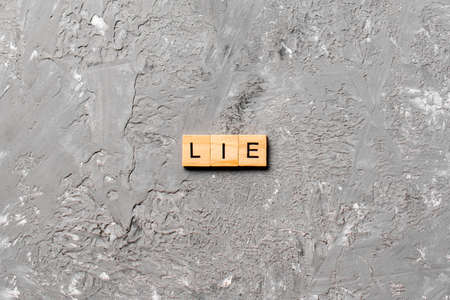 LIE word written on wood block. LIE text on cement table for your desing, concept.