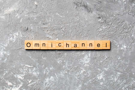OMNICHANNEL word written on wood block. OMNICHANNEL text on cement table for your desing, concept. 스톡 콘텐츠