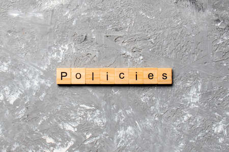 policies word written on wood block. policies text on table, concept.