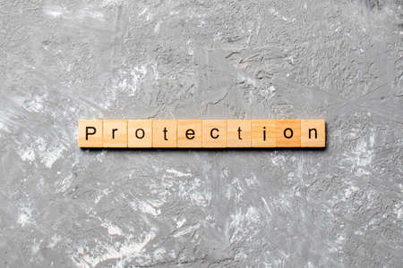 PROTECTION word written on wood block. PROTECTION text on cement table for your desing, concept.