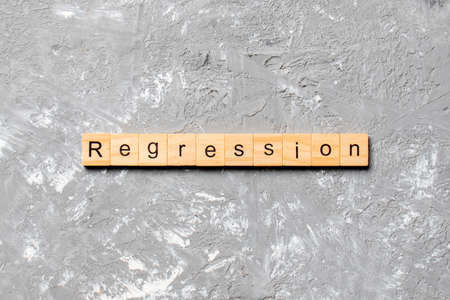 regression word written on wood block. regression text on cement table for your desing, concept.