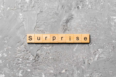 surprise word written on wood block. surprise text on table, concept.