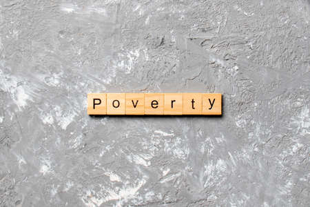Poverty word written on wood block. Poverty text on cement table for your desing, concept.