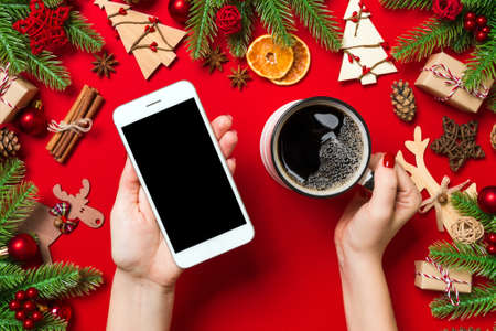 Top view of a woman holding a phone in one hand and a cup of coffee in another hand on red background. Christmas decorations and toys. New Year holiday concept. Mockup.
