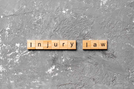 INJURY law word written on wood block. INJURY law text on table, concept.