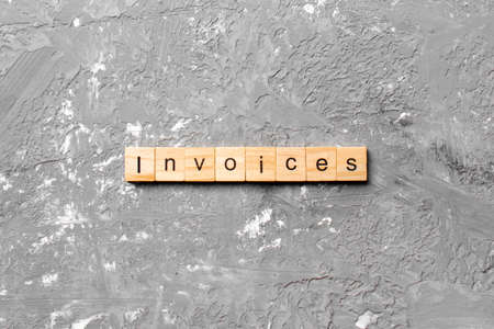 INVOICES word written on wood block. INVOICES text on cement table for your desing, concept.