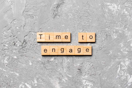 Time to engage word written on wood block. Time to engage text on table, concept.
