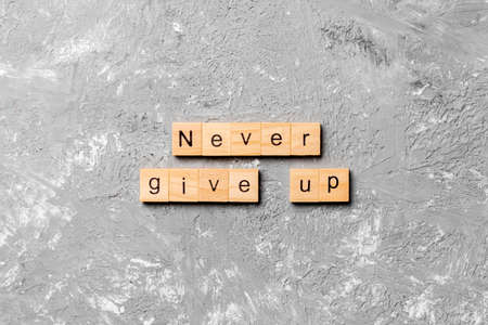 never give up word written on wood block. never give up text on cement table for your desing, concept.