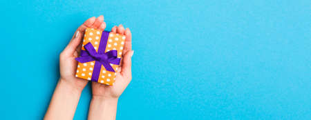 Woman arms holding gift box with colored ribbon on blue table background, top view and copy space for you design. Banque d'images