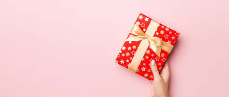 Female's hands holding striped gift box with colored ribbon on living coral background. Christmas concept or other holiday handmade present box, concept top view with copy space.