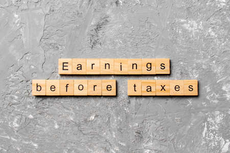 Earnings Before Taxes word written on wood block. abbreviation EBT text on cement table for your desing, concept. Stock fotó