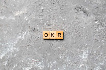 OKR word written on wood block. abbreviation of Objective Key Results text on cement table for your desing, concept.