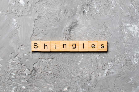 Shingles word written on wood block. Shingles text on cement table for your desing, concept.