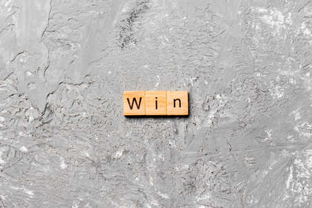 WIN word written on wood block. WIN text on cement table for your desing, concept.