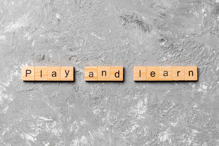 play and learn word written on wood block. play and learn text on table, concept.