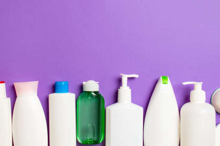Top view of cosmetic products in different jars and bottles on colored background. Close-up of containers with copy space.