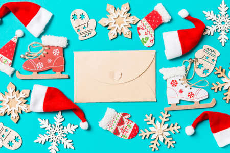 Top view of craft envelope with Christmas decorations and Santa hats on blue background. Happy holiday concept. 免版税图像