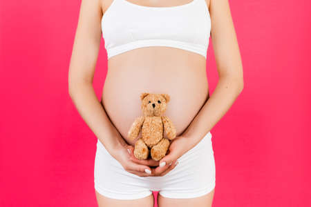 Cropped image of teddy bear in hand against pregnant woman's belly in white underwear at pink background. Waiting for a childbirth. Copy space.