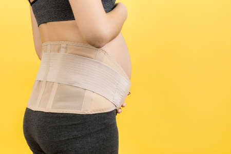 Back view of pregnant woman wearing pregnancy belt at yellow background with copy space. Close up of orthopedic abdominal support belt concept.