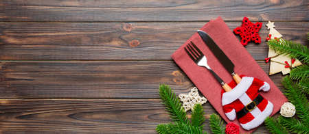 Top view of fork and knife put in santa clothes on napkin with christmas decorations and new year tree on wooden background. Banner holiday and festive concept with copy space.