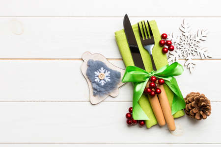 Top view of New Year dinner on wooden background. Festive cutlery on napkin with christmas decorations and toys. Family holiday concept with copy space. 免版税图像