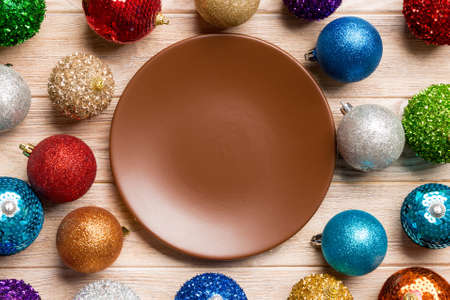 Top view of empty plate surrounded with colorful baubles on wooden background. New Year decorations. Christmas Eve concept.