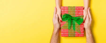 Top view of two people sharing a present on colorful background. Holiday and surprise concept. Copy space. 免版税图像