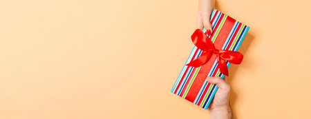 Top view of giving and receiving a present on colorful background. A man and a woman holding gift in hands. Festive concept with copy space.