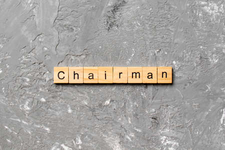 CHAIRMAN word written on wood block. CHAIRMAN text on cement table for your desing, concept.