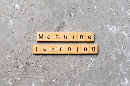 Machine learning word written on wood block. Machine learning text on cement table for your desing, concept. 免版税图像