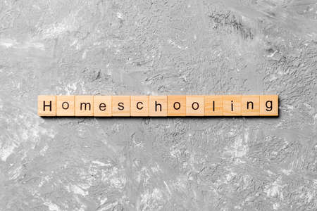 Homeschooling word written on wood block. Homeschooling text on cement table for your desing, Top view concept. 免版税图像