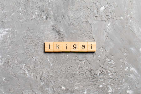 ikigai word written on wood block. ikigai text on table, concept.