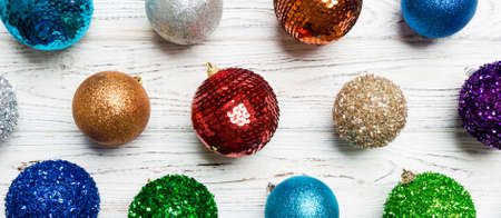 Top view Banner of colorful Christmas balls on wooden background. New Year time concept.