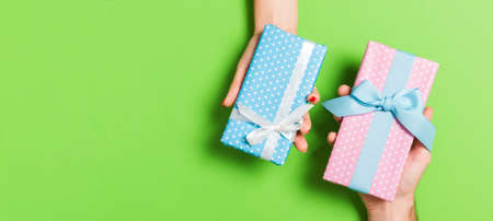 Top view of a woman and a man exchanging gifts on colorful background. Couple give presents to each other. Close up of making surprise for holiday concept.