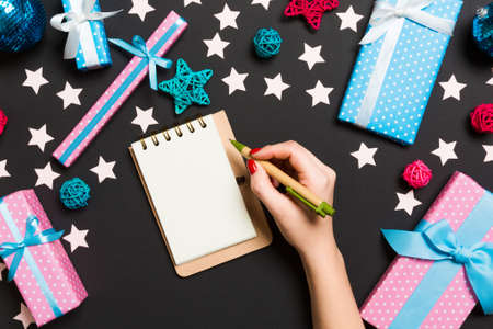 Top view of female hand making some notes in noteebok on colorful background. New Year decorations and toys. Christmas time concept. 版權商用圖片
