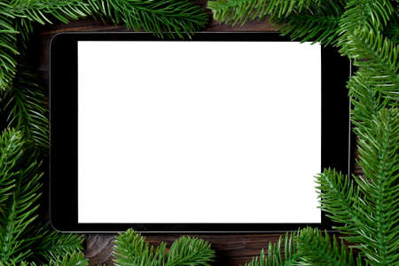 Top view of tablet decorated with a frame made of fir tree on wooden background. New Year time concept.