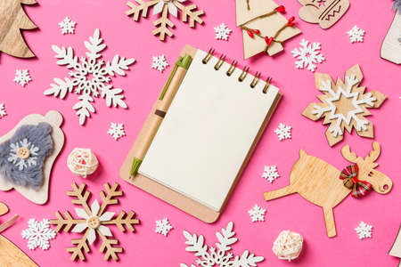 Top view of notebook on pink background made of holiday decorations and toys. Christmas ornament concept.
