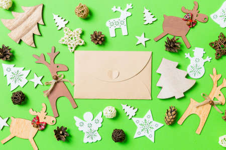 Christmas green background with holiday toys and decorations. Top view of craft envelope. Happy New Year concept. 版權商用圖片