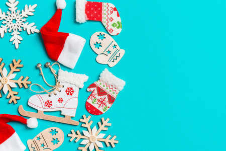 Top view of Christmas decorations and Santa hats on blue background. Happy holiday concept with copy space.