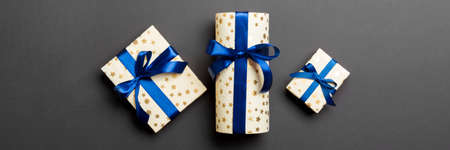 Gift box with blue bow for Christmas or New Year day on black background, top view.