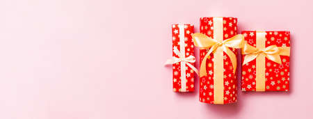 Gift box with gold bow in hands for Christmas or New Year day on pink background, top view. 版權商用圖片