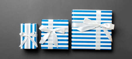 wrapped Christmas or other holiday handmade present in paper with White ribbon on black background. Present box, decoration of gift on colored table, top view.