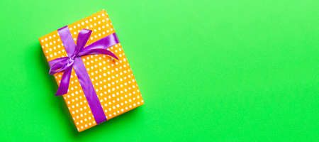 Top view Christmas present box with purple bow on green background with copy space.