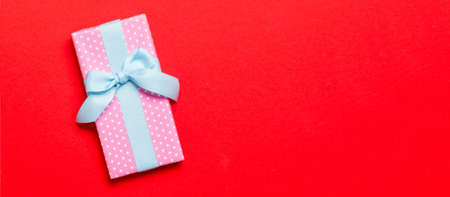 wrapped Christmas or other holiday handmade present in paper with blue ribbon on red background. Present box, decoration of gift on colored table, top view with copy space.