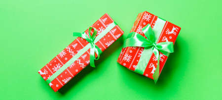 wrapped Christmas or other holiday handmade present in paper with green ribbon on green background. Present box, decoration of gift on colored table, top view.